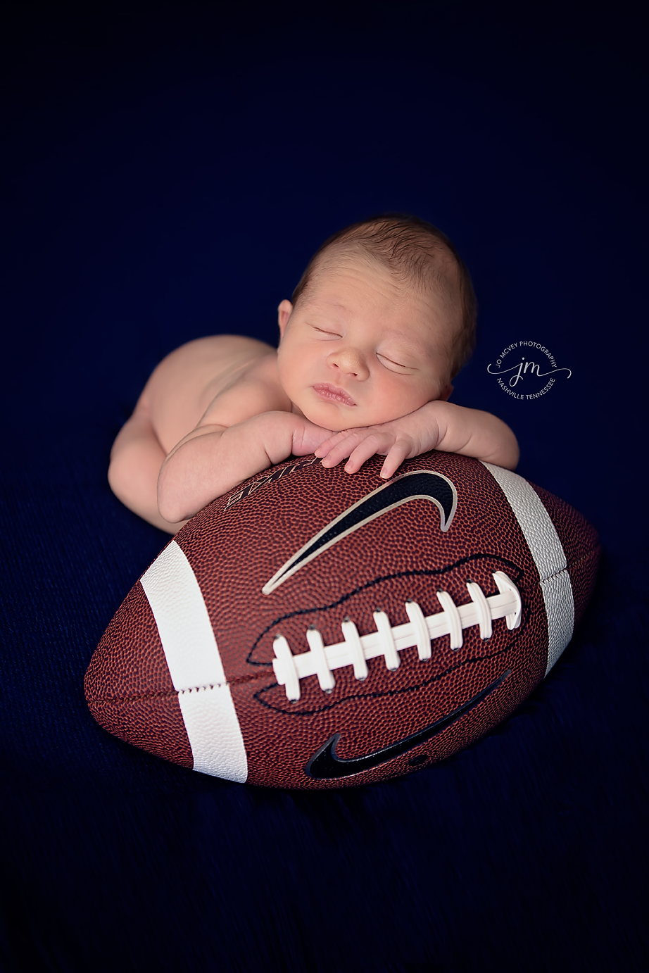 Newborn resting on football - Nashville Baby Photographer | Jo McVey Photography