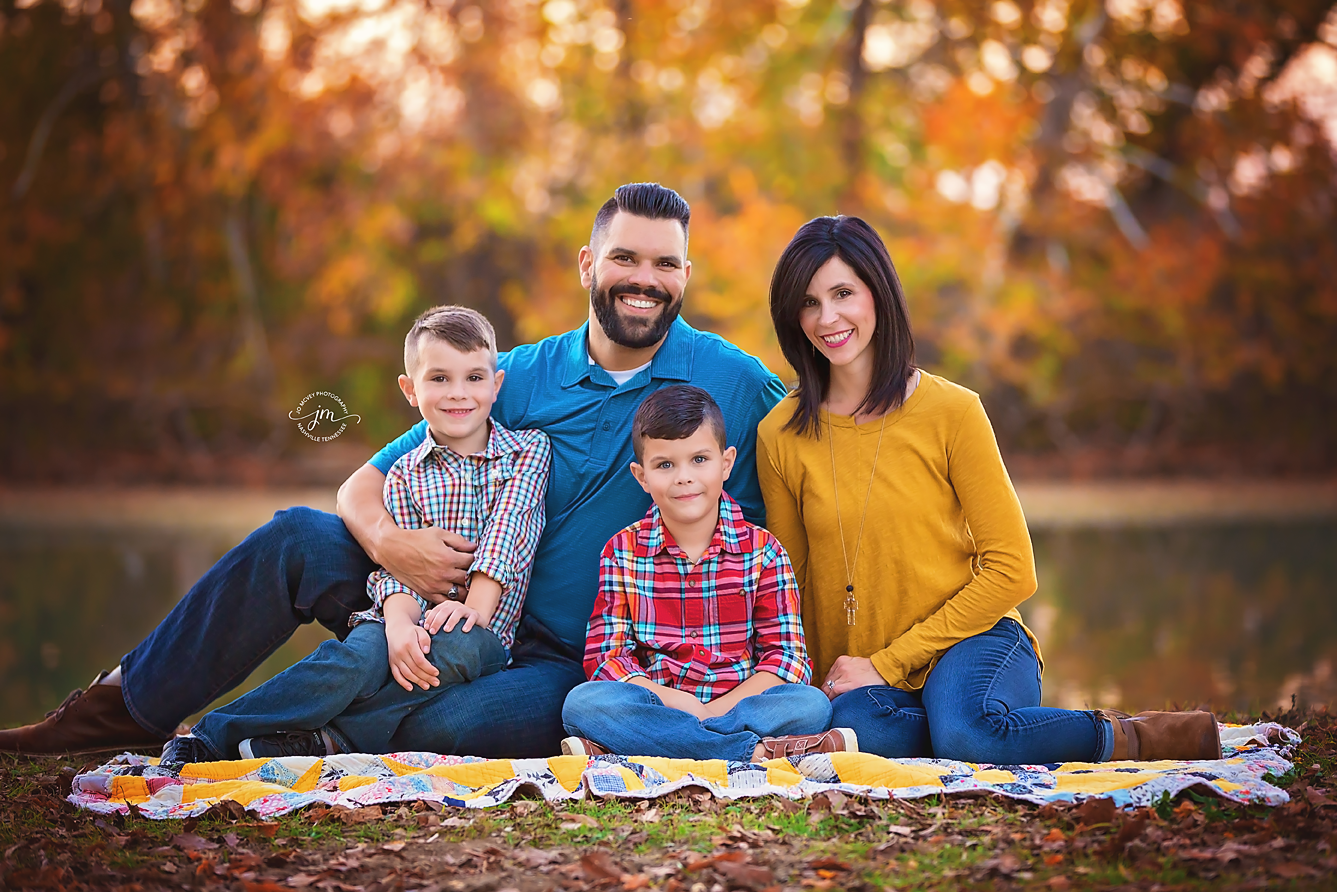 Family of 4 sitting on quilt near creek - Nashville Family Photographer | Jo McVey Photography