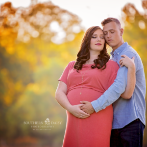 Expectant couple embracing in front of autumn leaves - Nashville maternity photographer