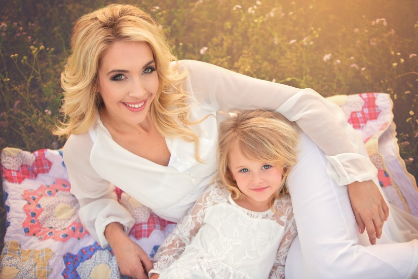 Mommy and me with white dresses laying on quilt - Nashville Family Photographer