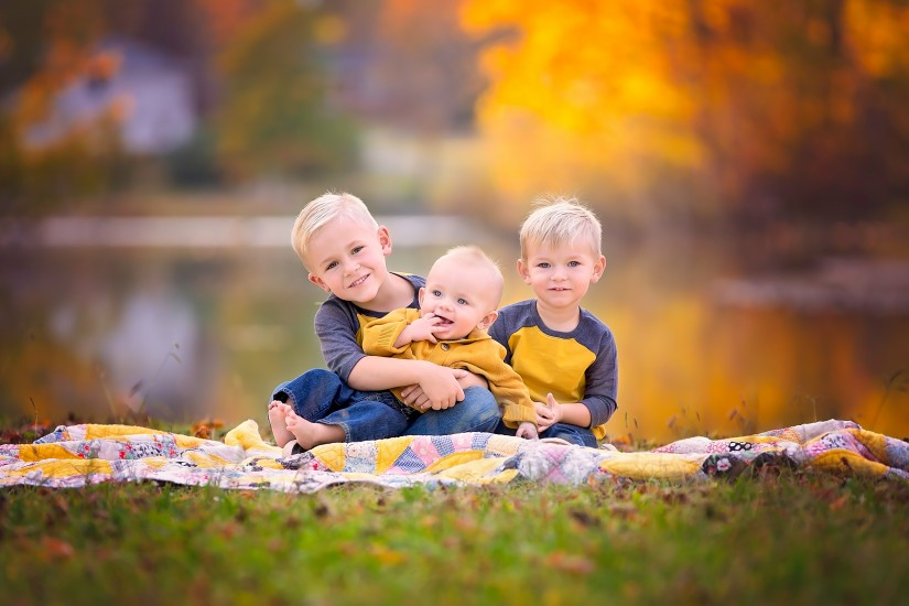 Three young brothers sitting on quilt in fall setting - Nashville Family Photographer